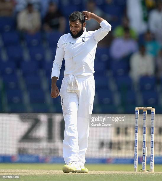 Adil Rashid of England reacts after being hit to the boundary during day two of the 1st Test between Pakistan and England at Zayed Cricket Stadium on...