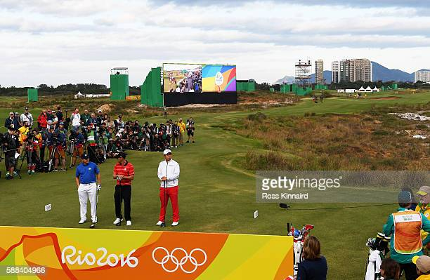 Adilson da Silva of Brazil, Graham Delaet of Canada, and Byeong Hun An of Korea prepare to play from the first tee during the first round of men's...
