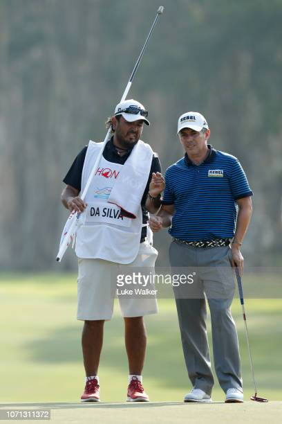 Adilson Da Silva of Brazil lines up a putt with his caddie on the 6th green during day two of the Honma Hong Kong Open at The Hong Kong Golf Club on...
