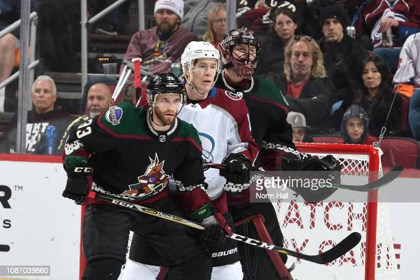 Adin Hill and Alex Goligoski of the Arizona Coyotes looks for the puck while battling with Matt Calvert of the Colorado Avalanche at Gila River Arena...