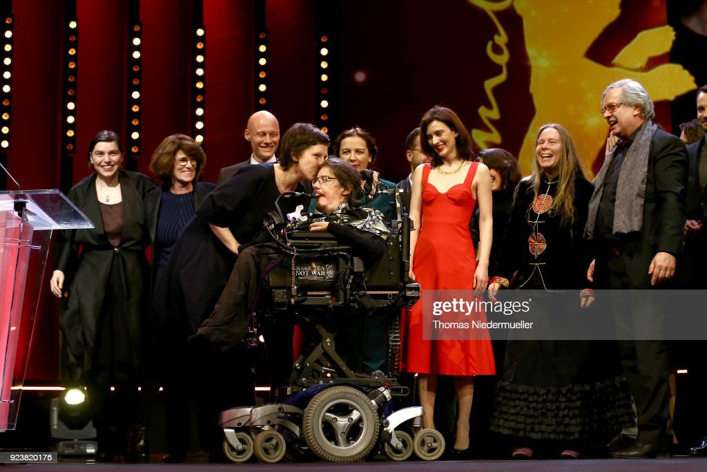 Adina Pintilie (C) winner of the Golden Bear for Best Film for 'Touch me not' kisses actor Christian Bayerlein on stage at the closing ceremony during the 68th Berlinale International Film Festival Berlin at Berlinale Palast on February 24, 2018 in Berlin, Germany.