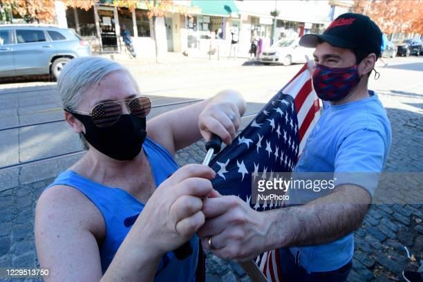 Adina Silberstein and Karen Howard repair an American flag to celebrate the historic victory of Joe Biden and Kamala Harris in the 2020 US...