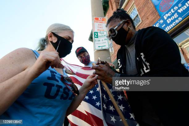 Adina Silberstein, Karen Howard and Christian Eckman repair an American flag to celebrate the historic victory of Joe Biden and Kamala Harris in the...