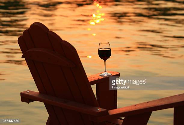 adirondack chair and wine at sunset by lake - sunset lake stock photos and pictures