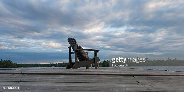 Adirondack chair on dock at lake