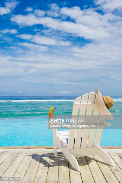 Adirondack chair with juice, sun hat and sunglasses near swimming pool