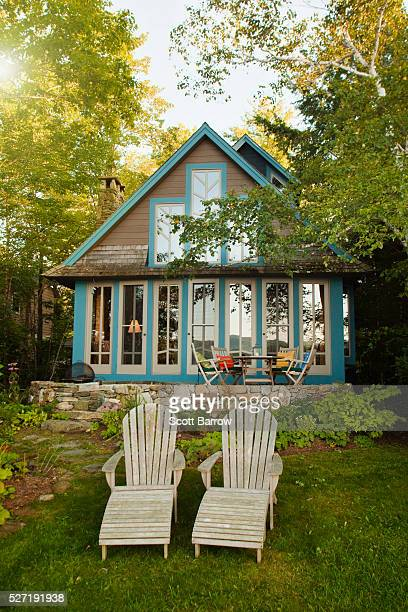 Adirondack chairs beside a summer cottage