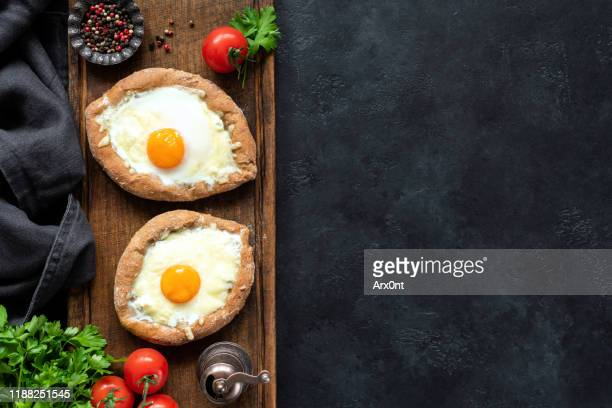 adjarian khachapuri on wooden serving board - georgian culture stock pictures, royalty-free photos & images
