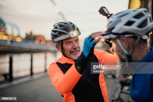 adjusting a cycle helmet light - cycling helmet stock photos and pictures