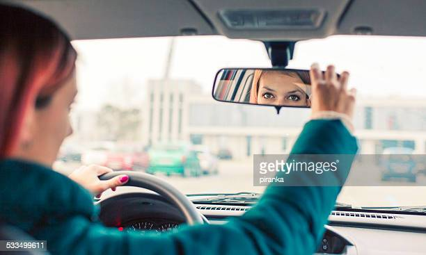 adjusting the rear view mirror - girl in mirror stock photos and pictures