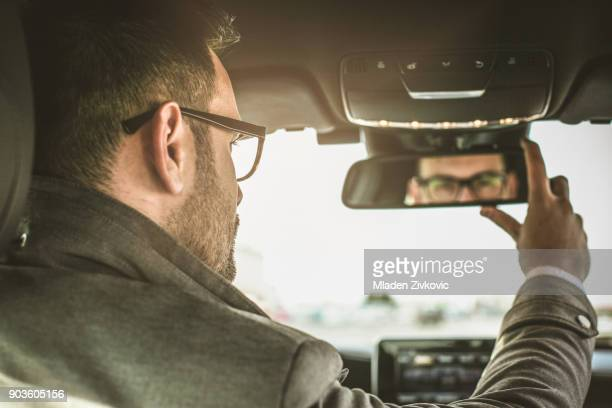 adjusts the mirror. - rear view mirror stock pictures, royalty-free photos & images