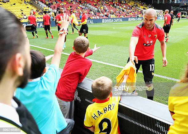 Adlene Guedioura of Watford gives his shirt to a young Watford fan during the Premier League match between Watford and Arsenal at Vicarage Road on...
