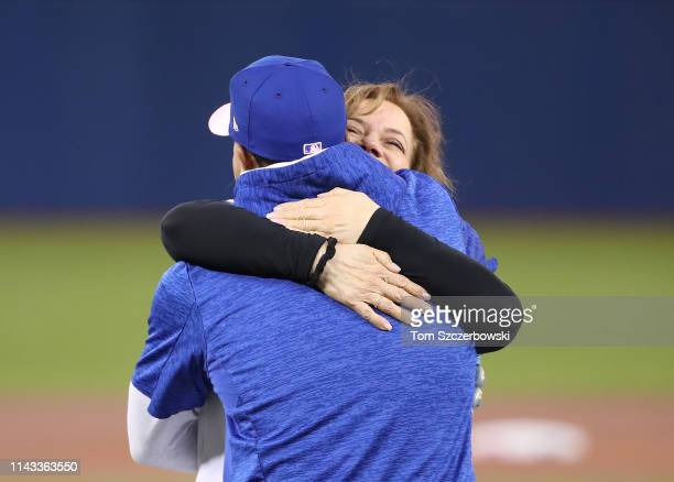 Adlin Auffant the mother of Marcus Stroman of the Toronto Blue Jays shares a hug with her son after throwing out the first pitch on Mothers Day...