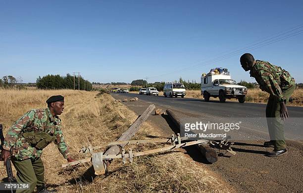 Administration police remove a road block as a convoy of vehicles carrying Kikuyu people leave Eldoret for Nairobi on January 6 2008 in Kenya After...