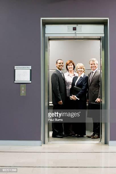 Administrative workers smiling in elevator