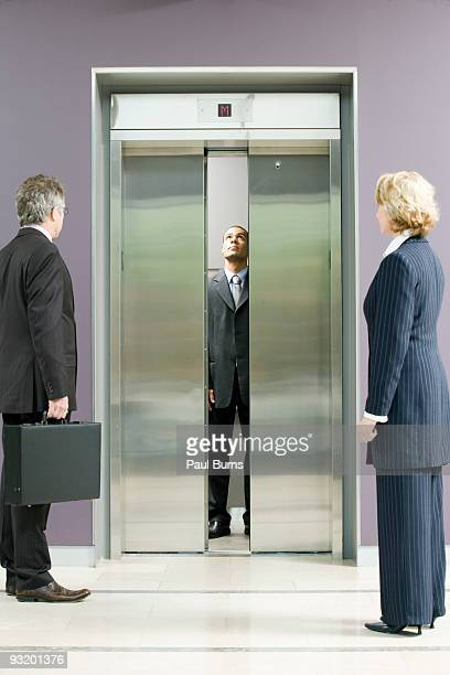 administrative workers waiting for elevator - エレベーター ストックフォトと画像