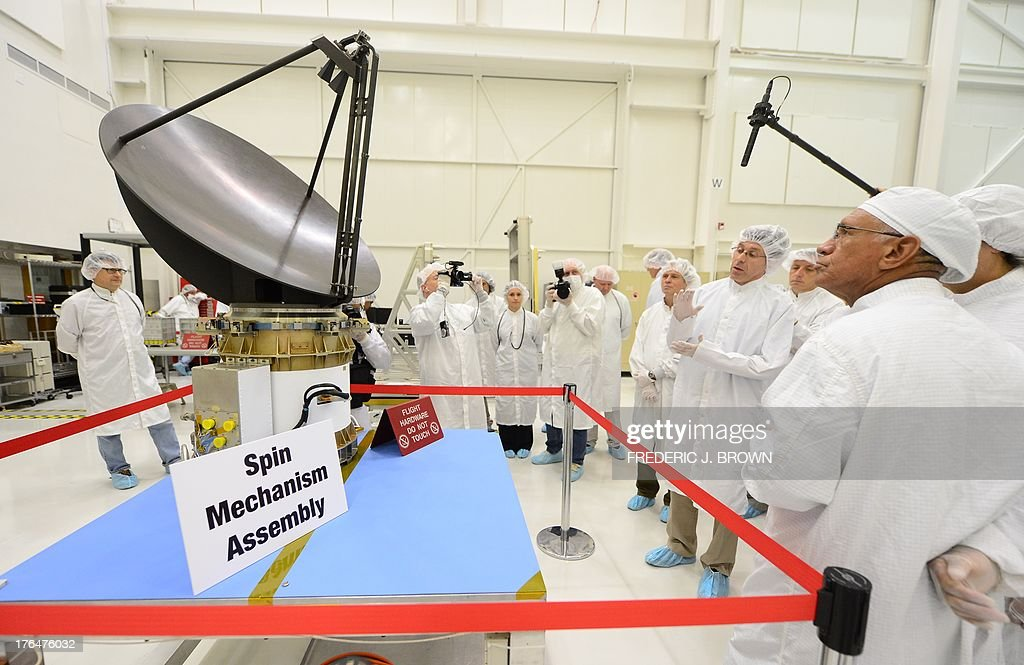Administrator Charles Bolden (R) tours the Spacecraft Assembly Facility Cleanroom at the Jet Propulsion Laboratory in Pasadena, California on August 13, 2013, to see the progress and assembly of the Soil Moisture Active Passive (SMAP) satellite presently under construction and due to launch in October 2014. SMAP will produce global maps of soil moisture for tracking water availability around the planet, and will also detect winter freeze and spring thaw to track changes in growing season patterns, allowing scientists to determine how much carbon plants take up from the atmosphere each year. AFP PHOTO/Frederic J. BROWN