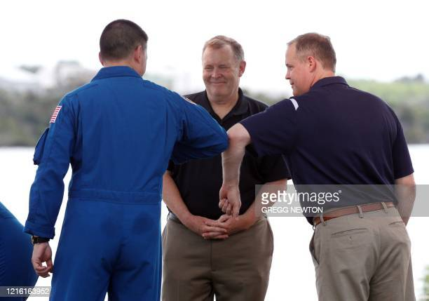 Administrator Jim Bridenstine bumps elbows with astronaut Kjell Lindgren as NASA Deputy Administrator James Morhard watches during a prelaunch...