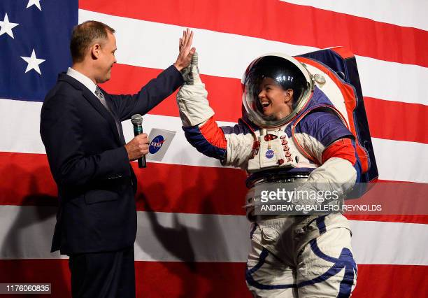 NASA administrator Jim Bridenstine welcomes Advance space suit engineer Kristine Davis to the stage during a press conference displaying the next...