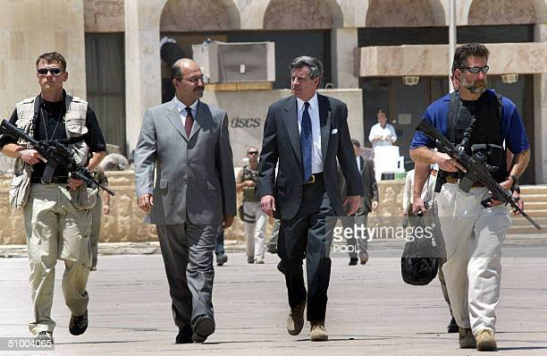 Administrator L Paul Bremer is escorted to an Air Force plane by Iraqi Deputy Prime Minister Barham Salih at the Baghdad International Airport for...