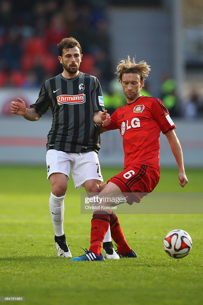 Admir Mehmedi of Freiburg challenges Simon Rolfes of Leverkusen during the Bundesliga match between Bayer 04 Leverkusen and SC Freiburg at BayArena on February 28, 2015 in Leverkusen, Germany.