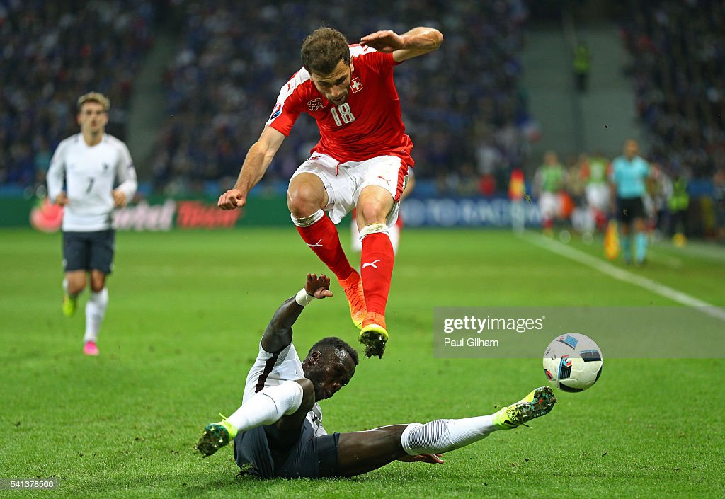 Admir Mehmedi of Switzerland is tackled by Bacary Sagna of France during the UEFA EURO 2016 Group A match between Switzerland and France at Stade Pierre-Mauroy on June 19, 2016 in Lille, France.