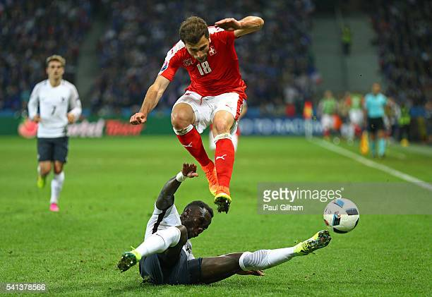 Admir Mehmedi of Switzerland is tackled by Bacary Sagna of France during the UEFA EURO 2016 Group A match between Switzerland and France at Stade...