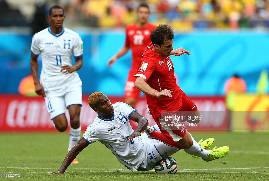Admir Mehmedi of Switzerland is tackled by Brayan Beckeles of Honduras during the 2014 FIFA World Cup Brazil Group E match between Honduras and Switzerland at Arena Amazonia on June 25, 2014 in Manaus, Brazil.