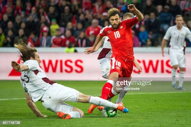 Admir Mehmedi vies with Kaspars Gorkss during the World Cup Qualifiers group match between Switzerland and Latvia on March 25 at Stade de Geneva in...