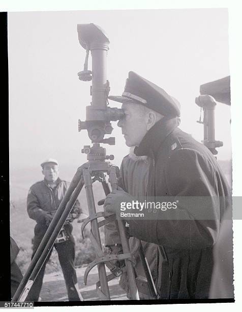 Admiral Arthur W Radford chairman of the US Joint Chiefs of Staff observes communist positions through periscope binoculars at a Korean observation...