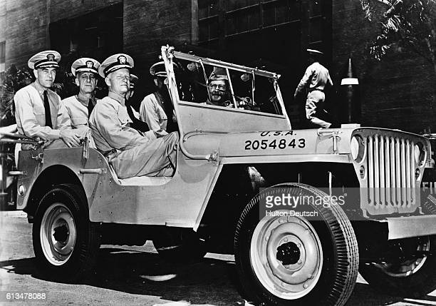 Admiral Chester William Nimitz the CommanderinChief of the US Pacific Fleet takes a ride around Pearl Harbor with his aidesdecamp in a jeep presented...