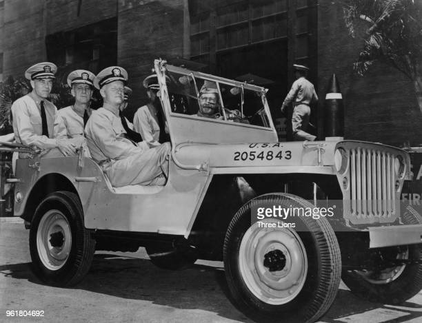Admiral Chester William Nimitz the CommanderinChief of the US Pacific Fleet takes a ride around Pearl Harbor in Hawaii with his aidesdecamp in a jeep...