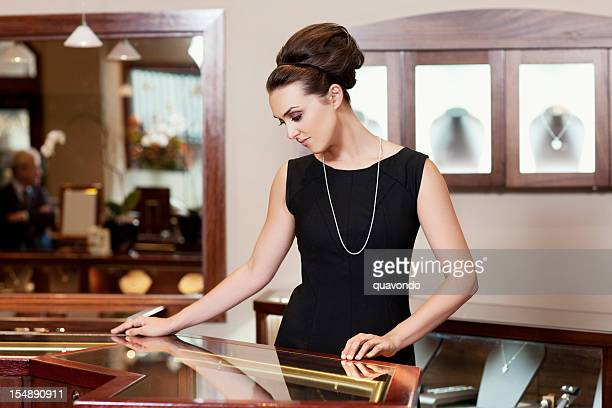 admiring, beautiful young woman in jewelry store, copy space - jewelry store stock pictures, royalty-free photos & images