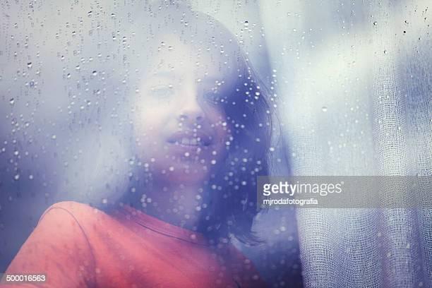admiring the rain against a window - mjrodafotografia fotografías e imágenes de stock