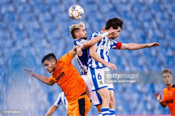 Adnan Januzaj and Aritz Elustondo of Real Sociedad battles for the ball with Maxi Gomez of Valencia CF during the La Liga Santander match between...