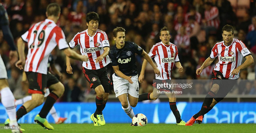 Adnan Januzaj of Manchester United in action with Ki Sung-Yeung and Emanuele Giaccherini of Sunderland during the Barclays Premier League match between Sunderland and Manchester United at the Stadium of Light on October 5, 2013 in Sunderland, England.