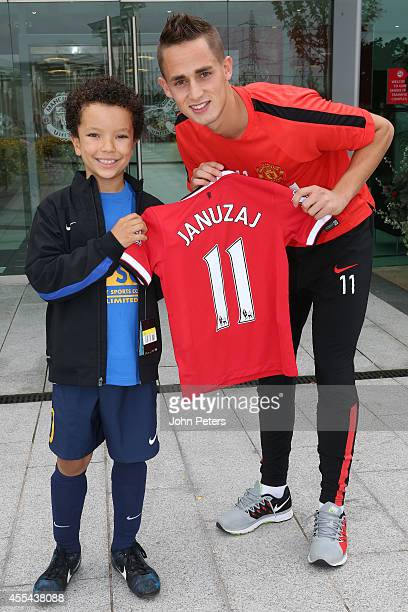 Adnan Januzaj of Manchester United presents young fan James Collins with a shirt with his new number on it after James bought one with his old number...
