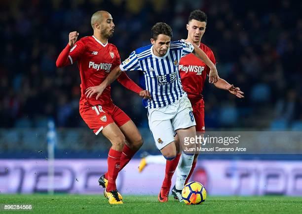 Adnan Januzaj of Real Sociedad being followed by Guido Pizarro of Sevilla FC and Sebastien Corchia of Sevilla FC during the La Liga match between...