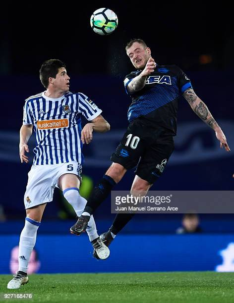 Adnan Januzaj of Real Sociedad competes for the ball with John Guidetti of Deportivo Alaves during the La Liga match between Real Sociedad and...