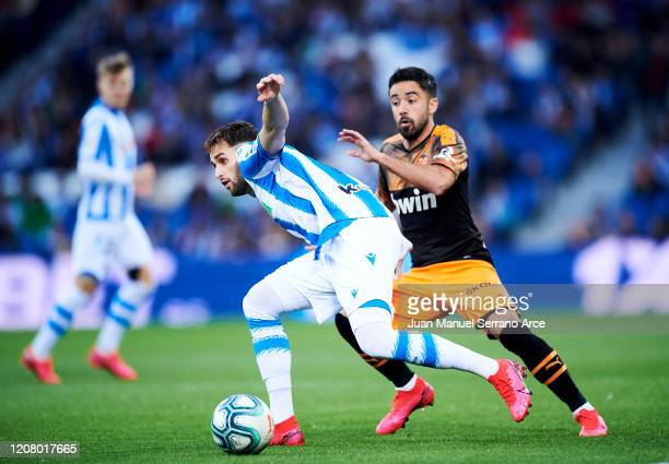Adnan Januzaj of Real Sociedad duels for the ball with Jaume Costa of Valencia CF during the Liga match between Real Sociedad and Valencia CF at...
