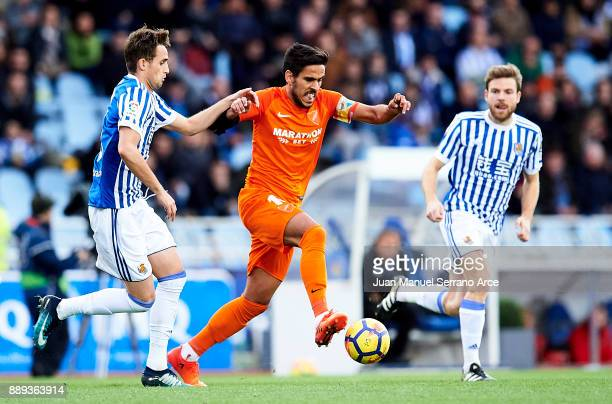 Adnan Januzaj of Real Sociedad duels for the ball with Jose Luis Garcia 'Recio' of Malaga CF during the La Liga match between Real Sociedad de Futbol...