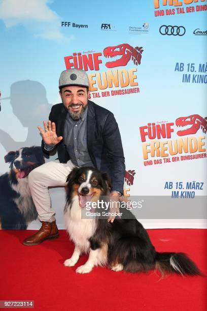 Adnan Maral with Bobby alias Timmy the dog during the 'Fuenf Freunde und das Tal der Dinosaurier' premiere at Mathaeser Kino on March 4 2018 in...