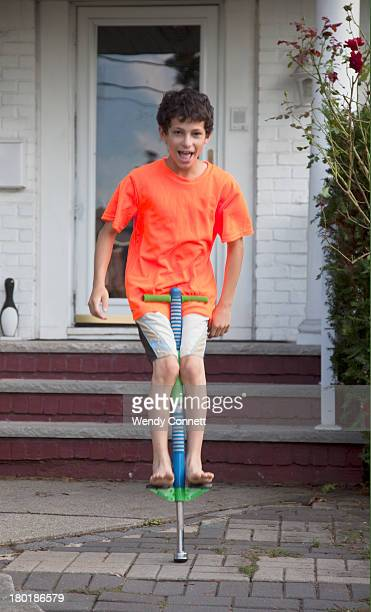 Adolescent boy playing on pogo stick