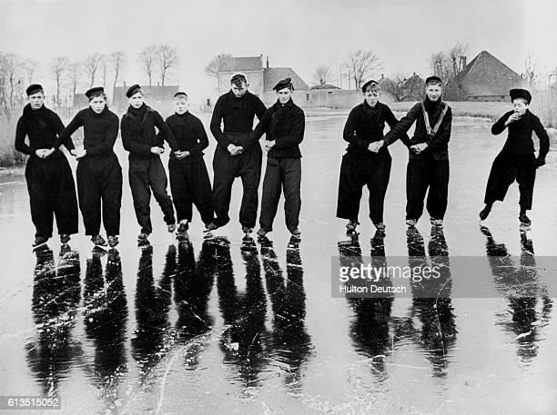 Adolescent boys ice skate on a frozen canal in Vollendam Netherlands | Location Vollendam Netherlands