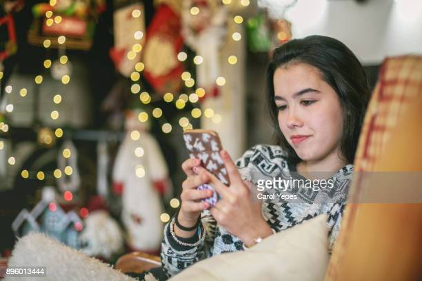 adolescent girl using smartphone at home in winter - hot spanish women stock pictures, royalty-free photos & images