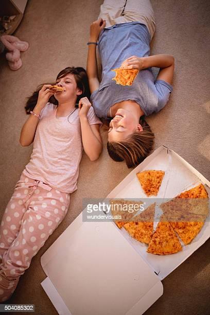 Teenager-Mädchen auf dem Boden liegen in take-away-pizza