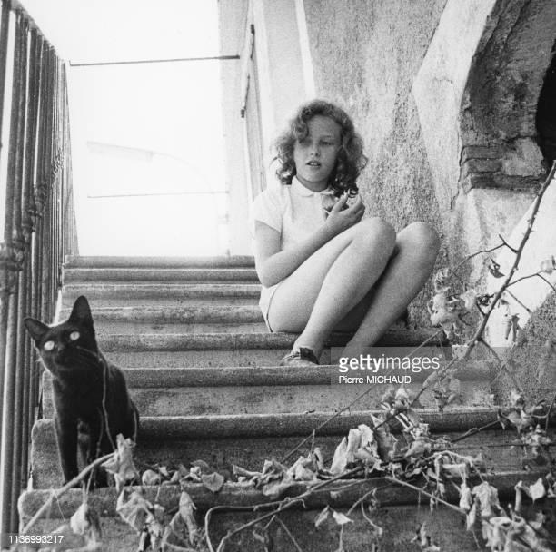 Adolescente assise dans un escalier avec son chat dans les années 1980 France