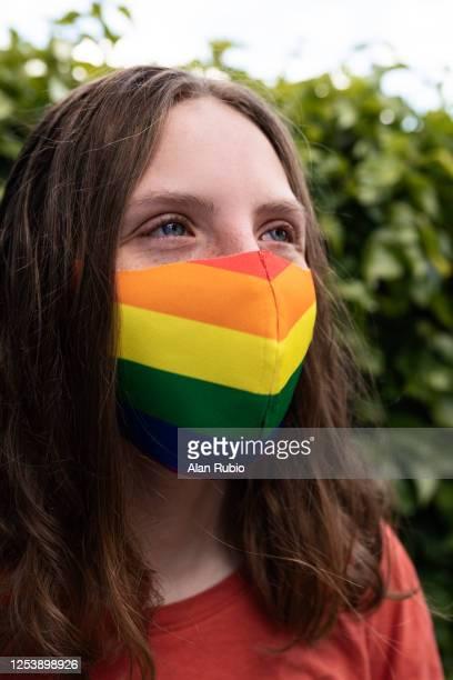 adolescente de ojos azules con una mascarilla con los colores del orgullo gay lgbt. - bisexuality fotografías e imágenes de stock