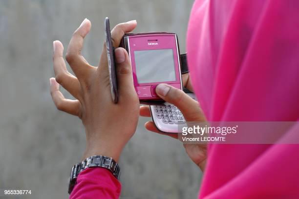 Adolescente indonésienne voilée écrivant un sms sur son smartphone à Painan au sud de lîle de Sumatra en Indonésie en septembre 2012