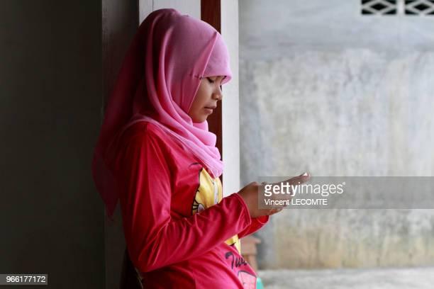 Adolescente indonésienne voilée utilisant son téléphone portable à la récréation à l'école de Basca à Painan au sud de lîle de Sumatra en Indonésie...